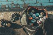 Fotografie rukavice a respirátor poblíž big bag s plechovky barva ve spreji