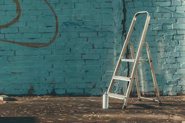 ladder and can with colorful spray paint near wall