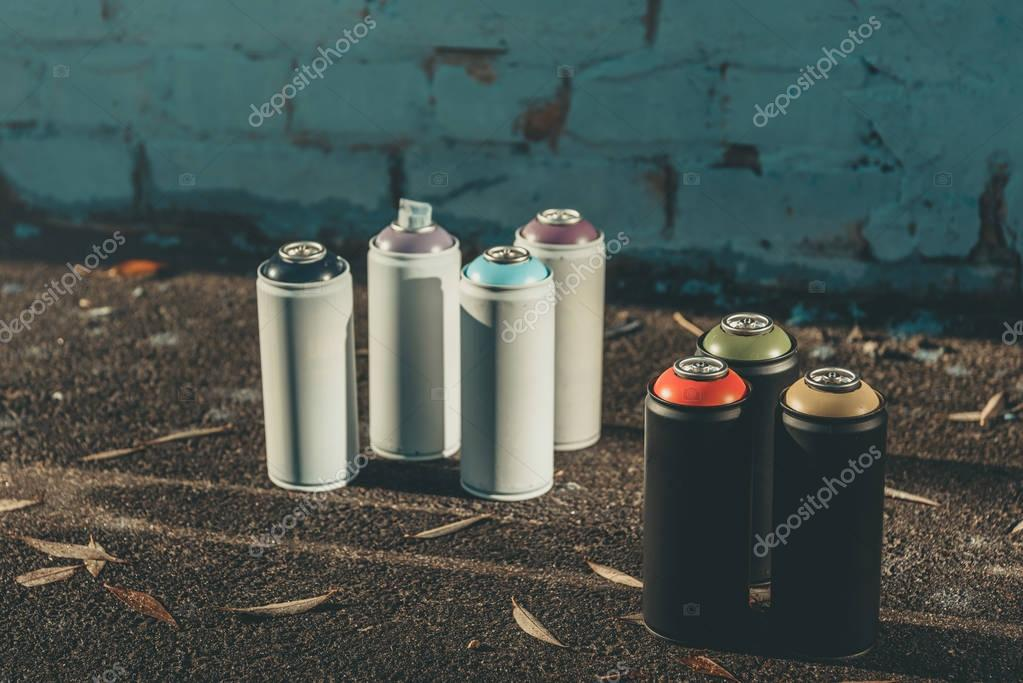 cans with colorful spray paint for graffiti on asphalt