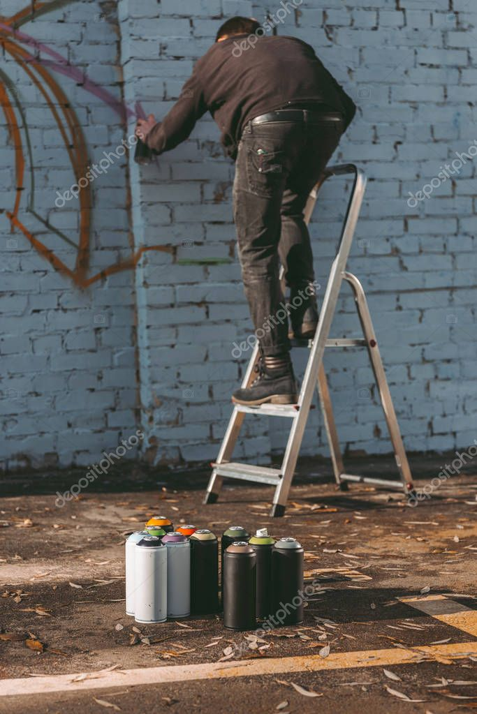 man standing on ladder and painting colorful graffiti on building