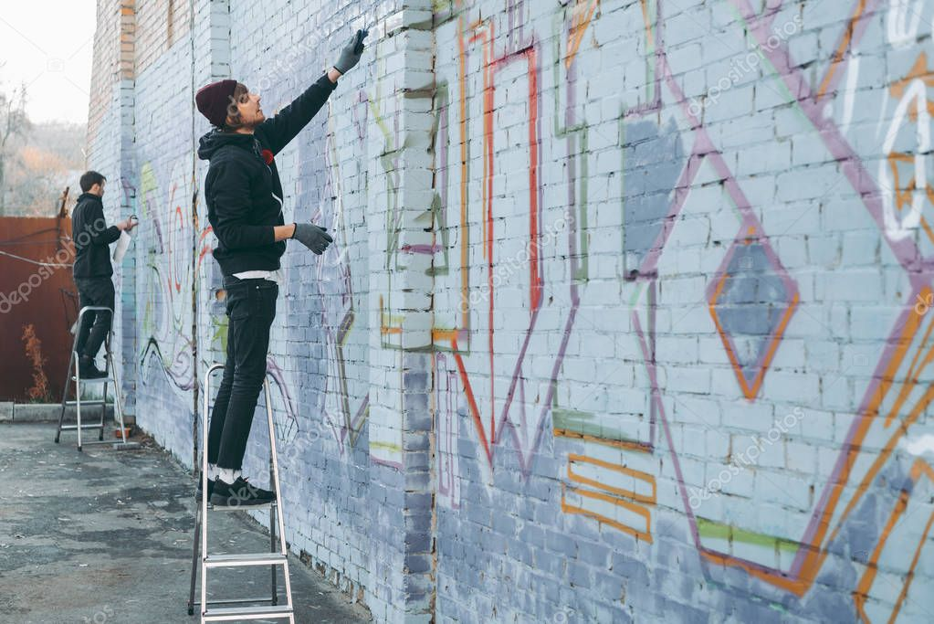 street artists standing on ladders and painting colorful graffiti on building