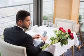 Fotografie mladý muž v obleku s smartphone čekání na přítelkyni v restauraci