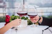 oříznuté záběr pár cinkání sklenic červeného vína, zatímco oslavuje st Valentýn v restauraci