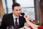 Fotografia vista parziale della donna che alimenta il ragazzo con il dessert su San Valentino giorno data romantica nel ristorante