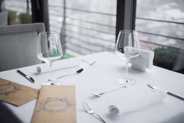 close up view of arranged cutlery, empty wineglasses and menu on table with white tablecloth in restaurant