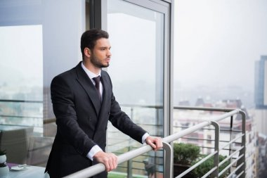portrait of young pensive man in suit standing at balcony