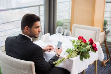 young man in suit with smartphone waiting for girlfriend in restaurant