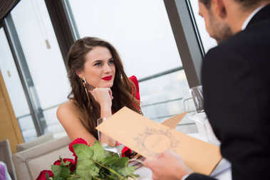 smiling woman looking at boyfriend during st valentine day date in restaurant