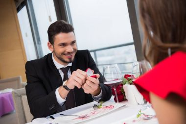 partial view of smiling man proposing to girlfriend on romantic date in restaurant on st valentine day