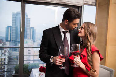 couple with glasses of red wine looking at each other celebrating st valentine day in restaurant