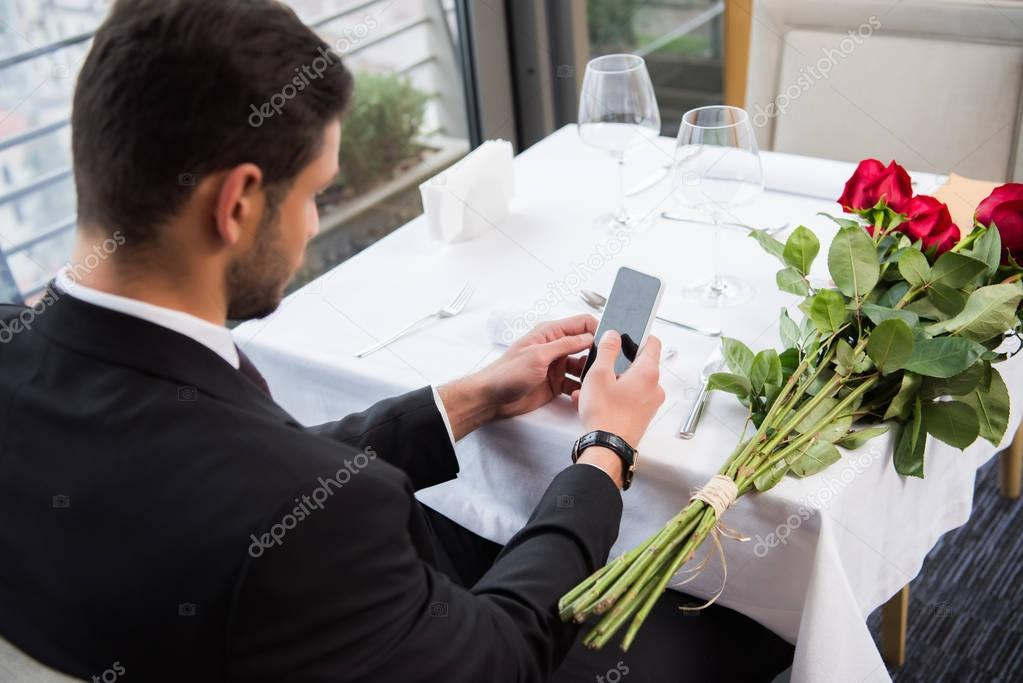 side view of man in suit using smartphone while waiting for girlfriend in restaurant