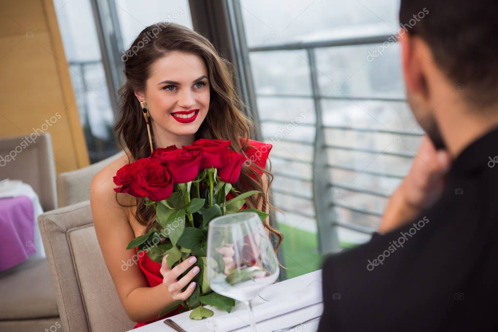 smiling woman with bouquet of roses during romantic date with boyfriend in restaurant, st valentine day