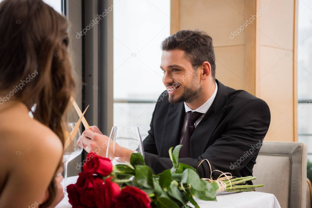 partial view of smiling man looking at girlfriend while reading menu on romantic date in restaurant, st valentine day