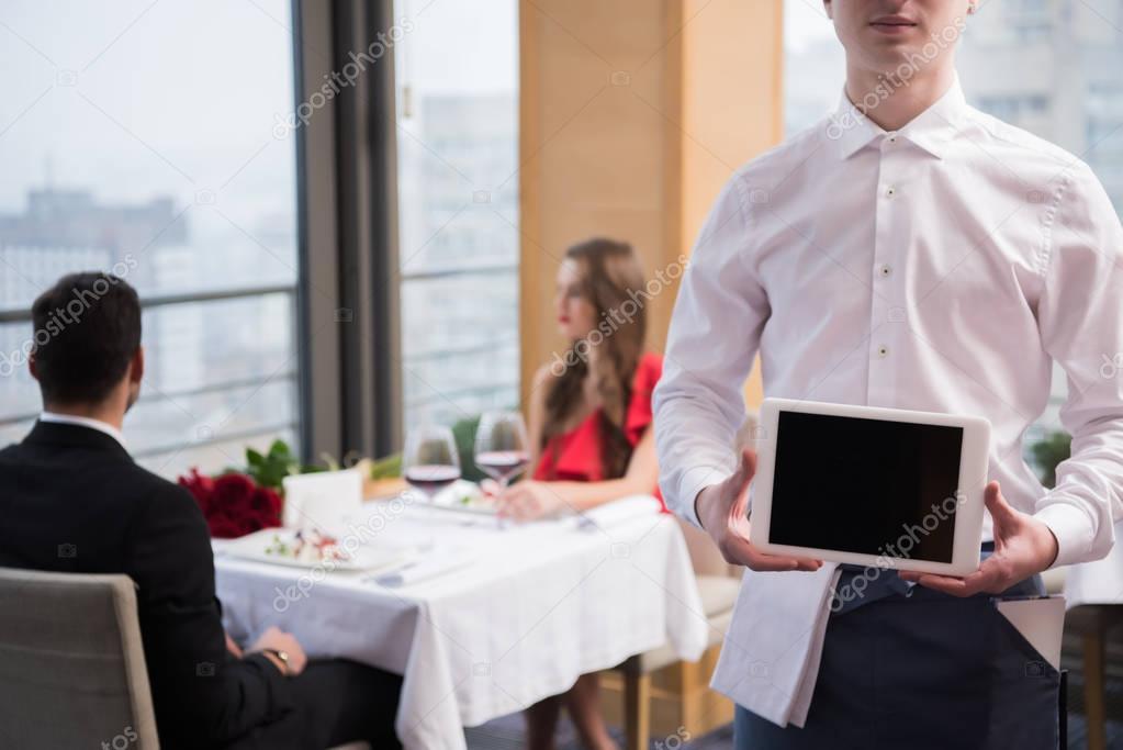 selective focus of waiter showing tablet in hands in restaurant