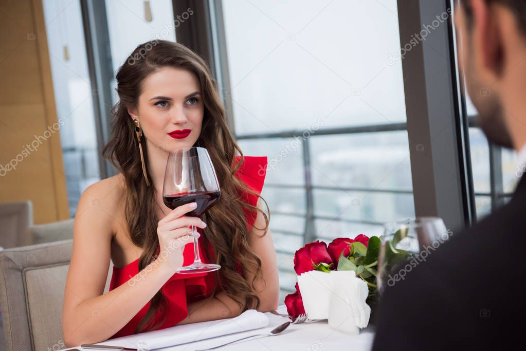 woman with glass of red wine looking at boyfriend during st valentine day date in restaurant