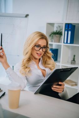 attractive businesswoman reading documents on clipboard