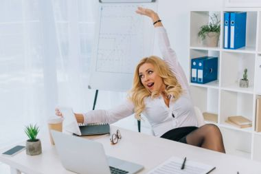 sexy businesswoman stretching and taking selfie at working place with tablet