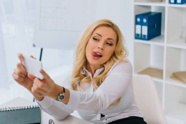 sexy businesswoman taking selfie at working place with smartphone and sticking tongue out