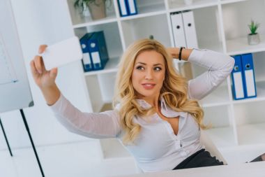 happy businesswoman taking selfie at working place with smartphone