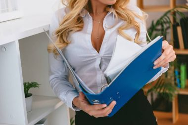 cropped image of sexy woman holding folder with documents