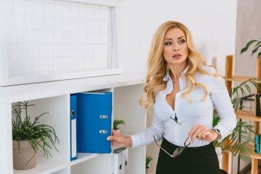 seductive woman taking folder from shelf