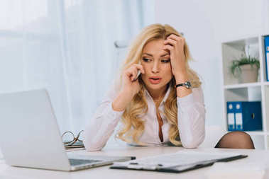 tired businesswoman talking by smartphone in office