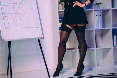 cropped image of sexy woman standing in stockings near diagram chart