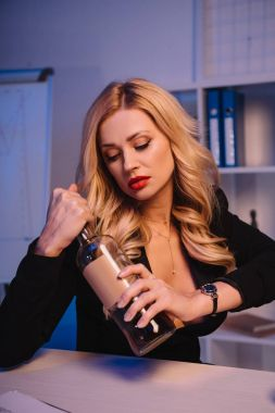 attractive sexy blonde woman opening bottle of whiskey in office