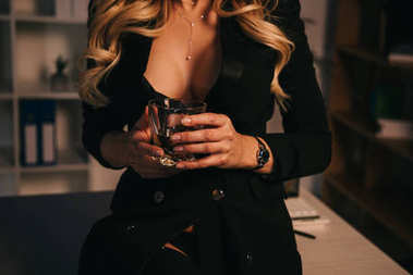 cropped image of attractive sexy woman holding glass of whiskey in office at evening