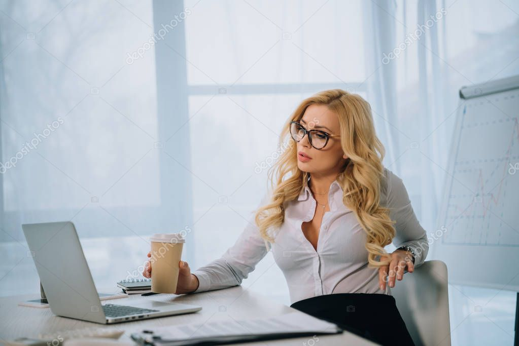 seductive businesswoman holding coffee in paper cup and looking at laptop