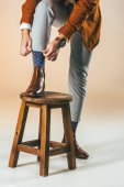 Fotografie partial view of man tying shoelaces while standing on wooden chair with one leg