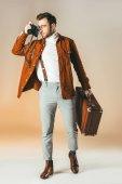 Fotografia elegante uomo con la valigia che cattura maschera sulla macchina fotografica