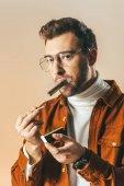 Fotografie Porträt von stilvollen Mann in Brillen zu beleuchten, Zigarre, die isoliert auf beige