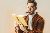 portrét mladého muže s doutník čtení knihy izolované na béžové