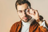 Fotografie selektiven Fokus der modische Mann betrachtet man Diamanten in der hand isoliert auf beige