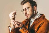 Fotografie Seitenansicht des modischen Mann betrachtet man Diamanten in der hand isoliert auf beige