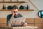 portrét šokován podnikatel čtenářský deník u stolu v kavárně