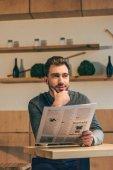 Fotografie portrét zamyšlený podnikatel koukal při čtení novin u stolu v kavárně