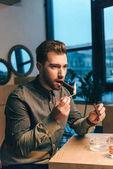Fotografie Porträt des jungen Mannes aufleuchten Zigarre beim Sitzen am Tisch im café