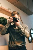 obscured view of stylish man taking picture on photo camera in cafe