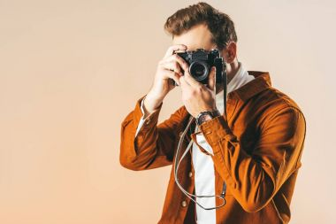 Obscured view of fashionable man taking picture on photo camera isolated on beige stock vector