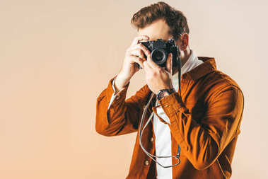 obscured view of fashionable man taking picture on photo camera isolated on beige