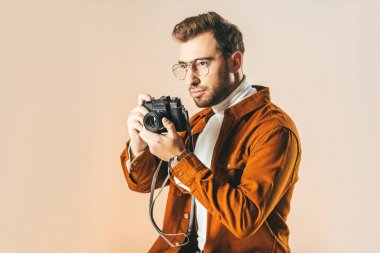 portrait of focused handsome man with photo camera in hands looking away isolated on beige