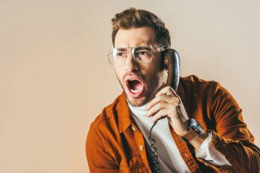 portrait of stylish man screaming while talking on telephone isolated on beige