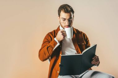 portrait of focused man drinking coffee while reading notebook in hand isolated on beige
