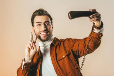 portrait of smiling man showing peace sign while pretending taking selfie in telephone tube isolated on beige
