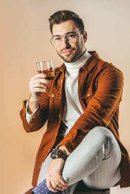 portrait of smiling stylish man with glass of cognac isolated on beige