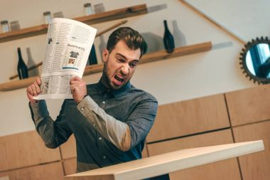 portrait of angry businessman throwing newspaper at table in cafe