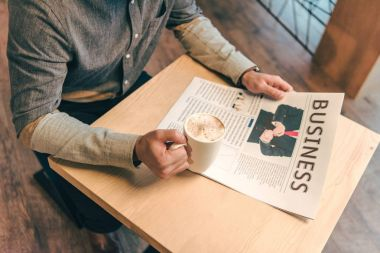 partial view of businessman with cup of coffee and business newspaper in cafe