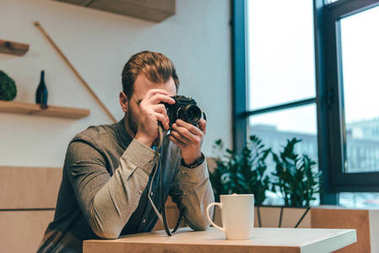 obscured view of man taking picture on photo camera in cafe